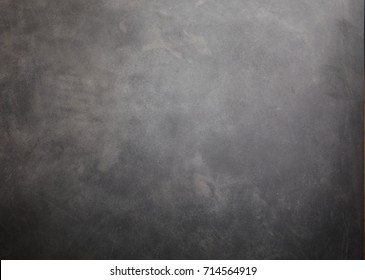 A rustic dark grey, plain textured background with copy space.
