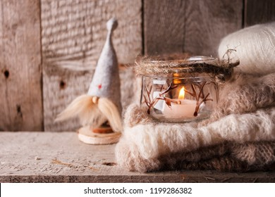 Rustic decoraton with handmade interior toy gnome, candle and warm knitted scarf on brown wooden background, perfect for scandi-chic style winter and autumn mood