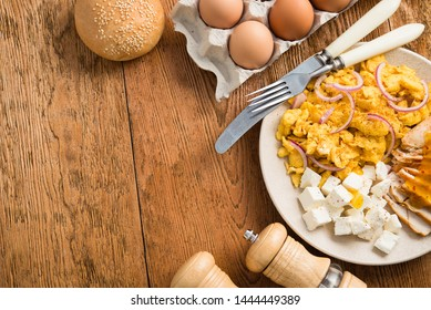 Rustic delicious scrambled eggs, chicken fillet and feta cheese on a wooden table. breakfast food. top view