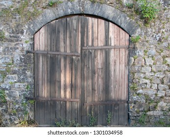 Rustic double wooden doors in stone archway in Carmarthenshire, Wales