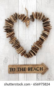 Rustic driftwood heart with wooden to the beach sign on distressed rustic white wood background.