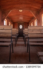 Rustic dusty old wagon interior with wooden steel seats and wooden floor, arched ceiling and glass windows as a monument from time of Lawrence of Arabia in Wadi Rum, Jordan