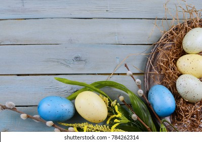 Rustic easter border on wooden background with yellow, green and blue colored eggs, artificial spring flower and pussy willows on a tarnished silver platter. Copy space.