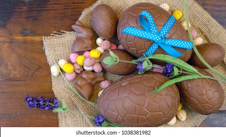 Rustic Easter overhead with chocolate Easter eggs and decorations on a wood table background