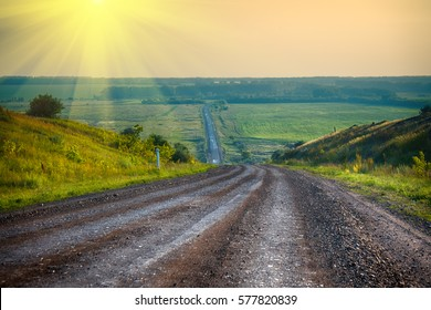 Rustic edge - dirt road (track) goes into field to rising sun