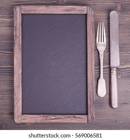 Rustic empty menu blackboard  with knife and fork on wooden background with copy space