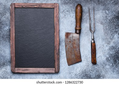 Rustic empty menu blackboard with vintage meat cleaver and fork on grunge concrete background with copy space