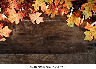 Rustic fall background of autumn leaves and decorative lights over a rustic wood table top  background. Image shot from overhead.