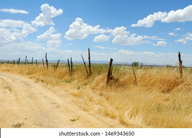 A rustic fence runs along a dirt road in southern Utah.  Southwestern landscape photography.