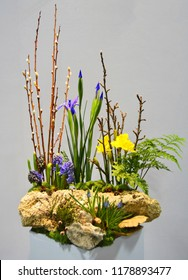 A rustic floral arrangement with rocks, ferns, pussy willows and minor accent colours.