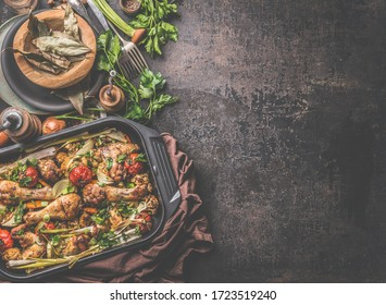 Rustic food background with oven roasted chicken and vegetables in black grill frying pan on rustic background . Top view