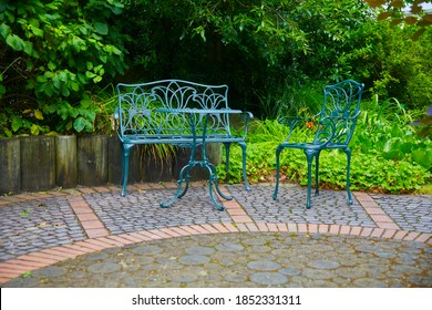 Rustikale Gartenterrasse mit Gartenstühlen und Tisch.