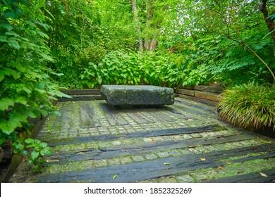 Rustic garden terrace with a stone table, wooden planks and paving stones.