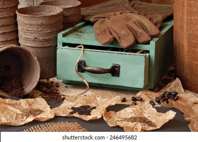 Rustic gardening still life with assorted seeds, organic starter pots, work gloves and vintage wooden box.  Selective focus on drawer with twine.