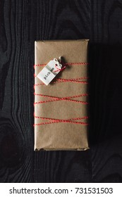 Rustic gift on dark wooden background with pick me tag