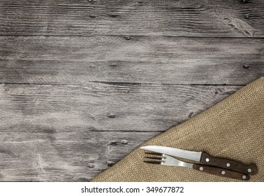 Rustic grange wood table top background with linen napkin, knife and fork.