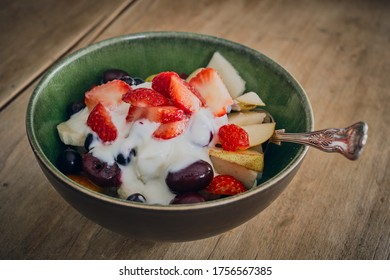 Rustic green bowl of fresh fruit and yogurt on a brown wooden table top