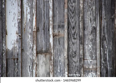 Rustic grey worn board and batten vertical siding background with white paint remnants