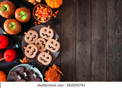 Rustic Halloween treat side border over a dark wood background with copy space. Top view. Variety of candied apples, cookies, candy and sweets.