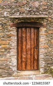 Rustic hand-hewn wood door set into a stone wall in Candal, one of Portugal's schist villages in the Aldeias do Xisto
