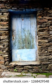 Rustic hand-hewn wood door set into a stone wall built from schist in Piodão, made of shale rocks stack, one of Portugal's schist villages in the Aldeias do Xisto.