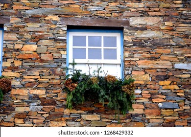Rustic hand-hewn wood window set into a stone wall built from schist in Piodão, made of shale rocks stack, one of Portugal's schist villages in the Aldeias do Xisto.