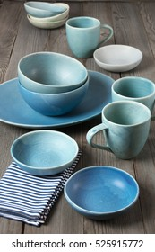 Rustic handmade blue ceramic dishware set and napkin on wooden table.