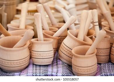 Rustic handmade wooden mortar and pestle on woven towel at street handicraft market