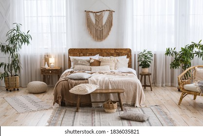 Rustic home design with ethnic decoration. Bed with pillows, wooden furniture, plants in pots, armchair and curtains on large windows in cozy bedroom interior, nobody, flat lay, panorama, free space - Shutterstock ID 1836035821