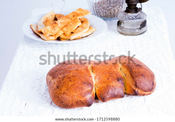 Rustic homemade baked Italian bread on a white lacy tablecloth