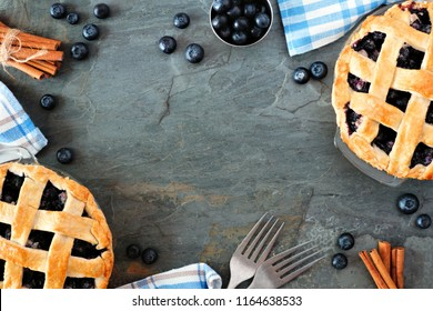 Rustic homemade blueberry pies with lattice pastry. Top view scene. Frame with copy space over a dark stone background.