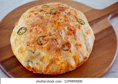 Rustic homemade bread with jalapeno peppers and cheddar cheese on round bread board in horizontal format.