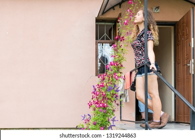 Rustic house home farm cottage dacha in Europe with stairs exterior entrance and open door with young woman smelling clematis climbing flowers