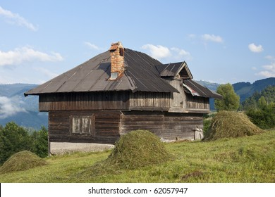 a rustic house on a grass field