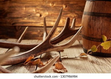 Rustic hunter house or bar decoration of deer antler, autumn yellow leaves and wooden barrel on the surface of old wooden table