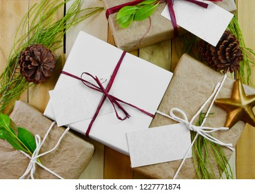 Rustic image of homemade wrapped gift on wooden background and green decoration