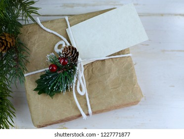 Rustic image of homemade wrapped gift on wooden background and green decoration with blank tag attached. Copy space.