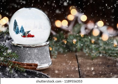Rustic image of a snow globe with old pick up truck hauling a Christmas tree surrounded by pine branches, cinnamon sticks and a warm gray scarf with gently falling snow flakes.