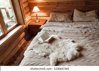 Rustic interior of log cabin bedroom with bed by big window. Opened book on sheep rug. Warm and cozy weekend morning in hotel.