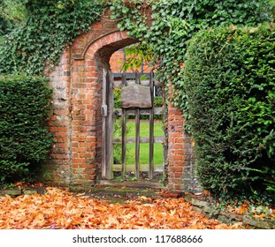 Rustic ivy covered arched gateway and red brick wall into an English garden
