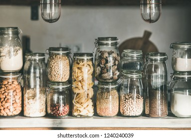 Rustic kitchen food storage arrangement. Grains, cereals, nut, dry fruit, flour, pasta kinds in glass jars over concrete kitchen counter. Clean eating, healthy, vegan, balanced diet concept