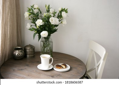 Rustic kitchen interior with flowers bouquet, tea mug and cake on round wood table.Neutral colors, simple style.