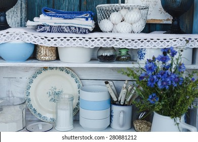 Rustic kitchen interior with shelves and flower.