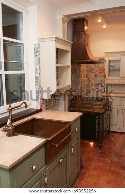 Rustic kitchen sink, stove and a copper range hood