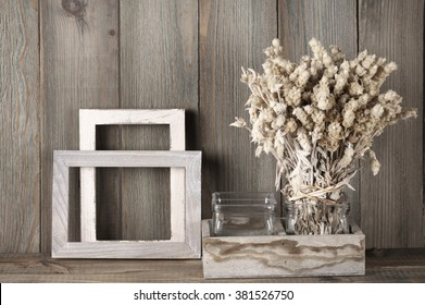 Rustic kitchen still life: dried flowers bunch and wood fotoframes against vintage wooden background.