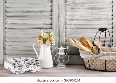 Rustic kitchen still life: wire basket with wooden spoons, jug with roses bunch, towels stack and lantern against vintage wooden shutters.