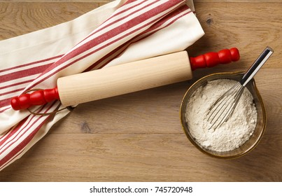 Rustic kitchen table countertop with striped cotton dish towel, wooden rolling pin and baking flour ingredients with stainless steel whisk in mixing bowl on wood background. Home cooking utensils.
