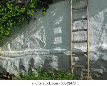 Rustic ladder against whitewashed wall