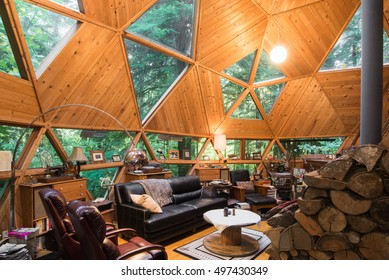 The rustic living room of an energy efficient dome house with a wood stove.
