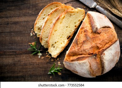 Rustic loaf of homemade bread sliced on dark wooden table. Overhead view